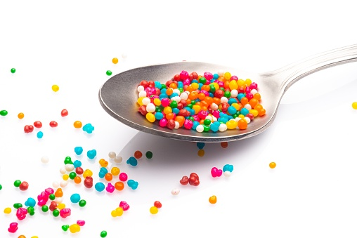 Sugar sprinkles on spoon over white background