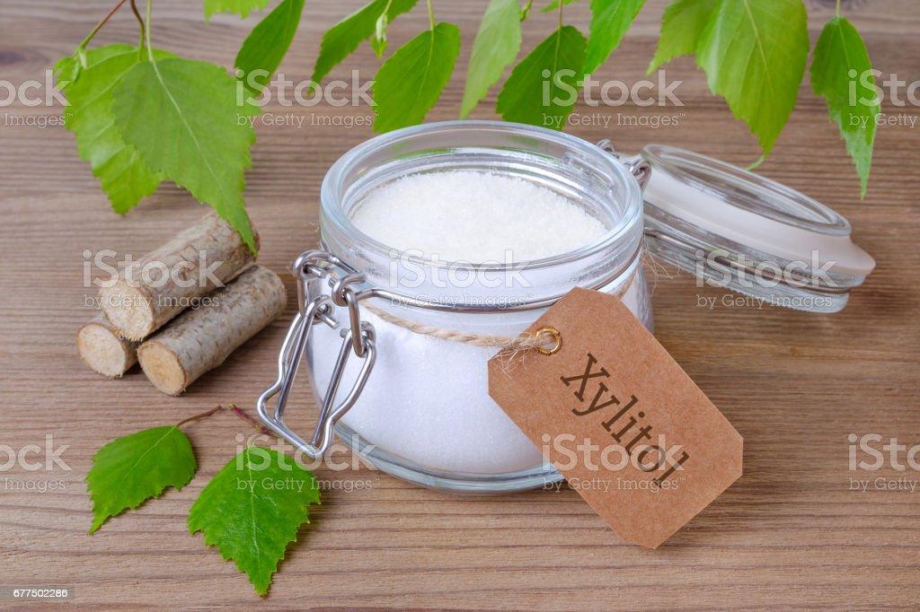 ersetzen Sie Zucker Xylit, ein Glas mit Birkenzucker, Liefs und Holz - Lizenzfrei Ausrüstung und Geräte Stock-Foto