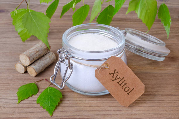 sugar substitute xylitol, a glass jar with birch sugar, liefs and wood stock photo