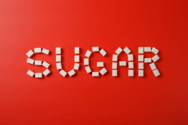 Zuckertext aus Zuckerwürfeln auf rotem Hintergrund – Foto