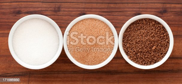 Top view of three bowls containing sugar varieties (white, brown and black)