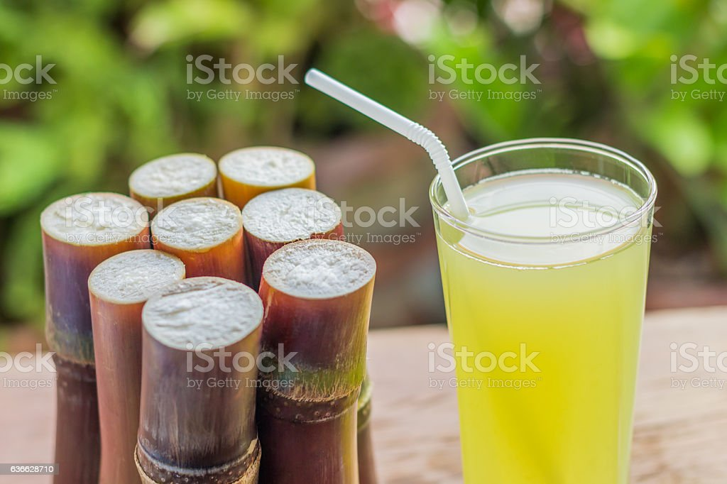 Sugarcane fresh juice with piece of sugarcane on wooden stock photo