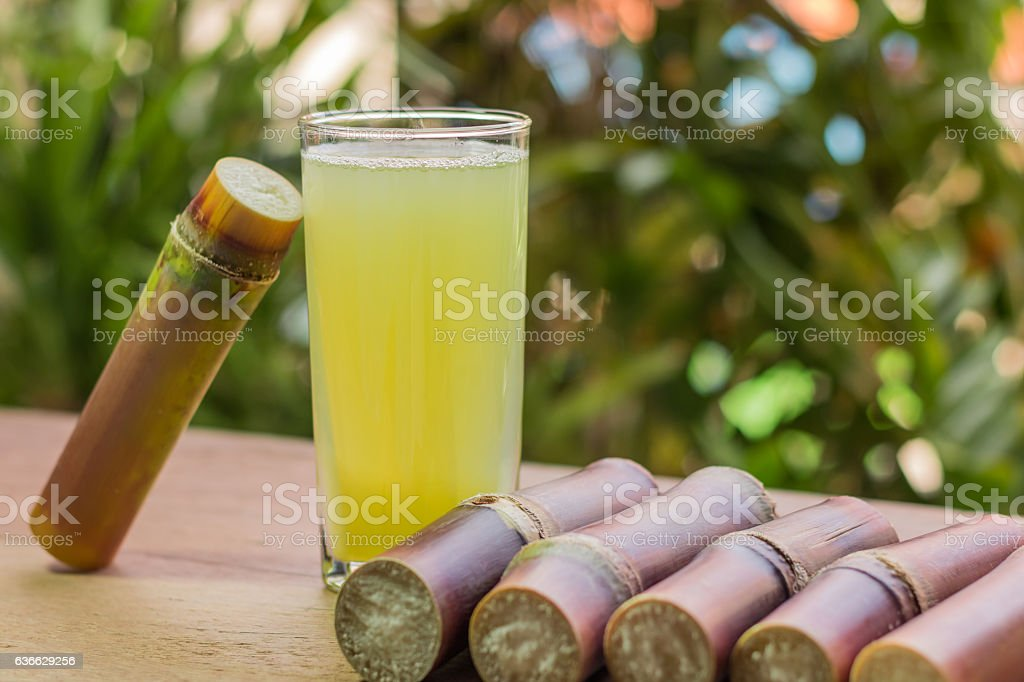 Sugarcane juice with piece of sugarcane on wooden background stock photo