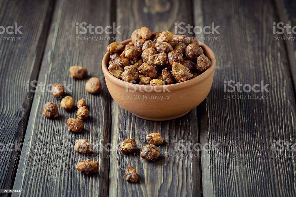 Sugared peanuts in a brown bowl on a wood background stock photo