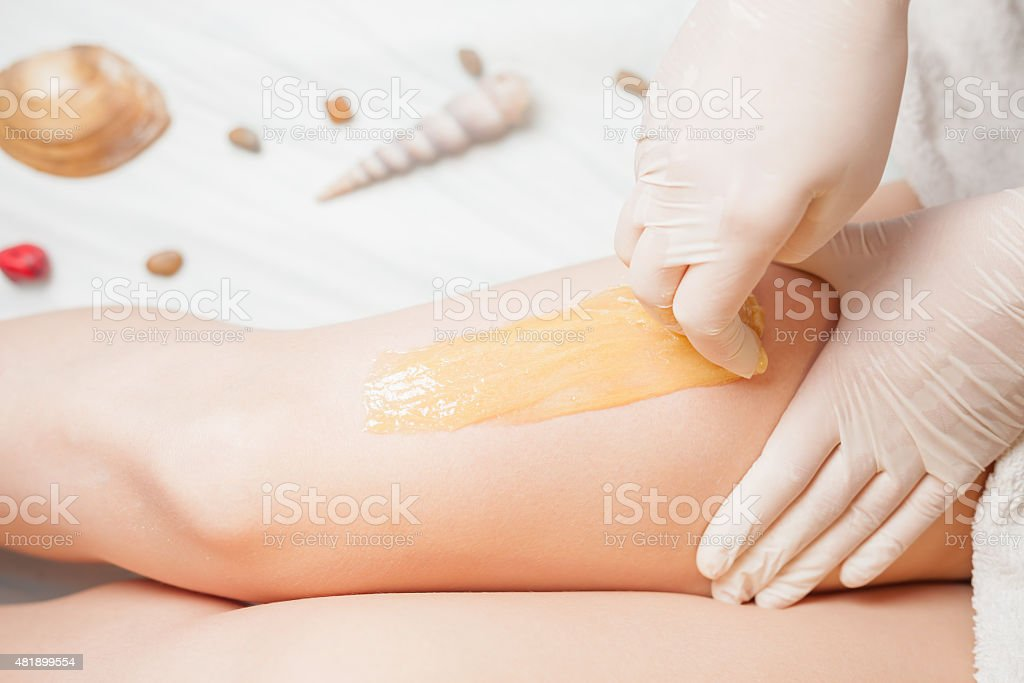 Sugaring epilation skin care with liquid sugar at legs stock photo