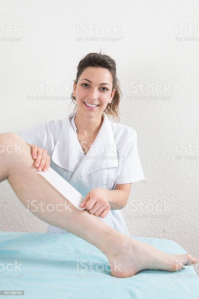 Sugaring: epilation with liquate sugar at legs. stock photo