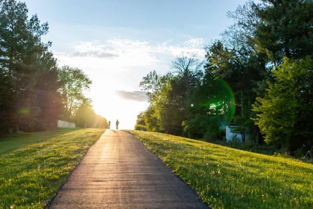 Caminhada de Sugarland Run Stream Valley Trail em Herndon, Virgínia, Condado de Fairfax na mola com estrada pavimentada do trajeto e silhueta do passeio dos pares - foto de acervo