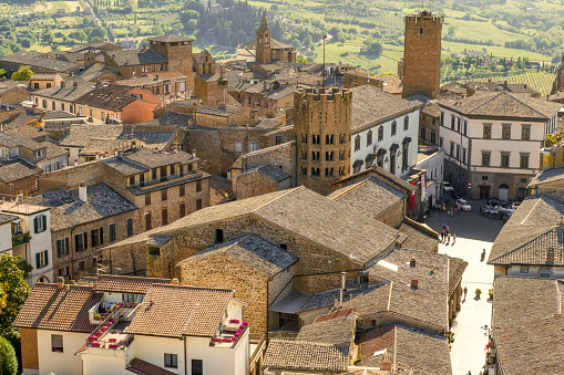 A suggestive and detailed aerial view of the historic heart of the medieval town of Orvieto and his valley in the Umbria region, central Italy. In the middle Piazza della Republica with the Town Hall and the decagonal bell tower of the church of Santi Andrea e Bartolomeo (Saints Andrews and Bartholomew). With a population of just 20,000 people, Orvieto is considered one of the most beautiful cities of art in Italy, founded since the Etruscan and Roman times on the flat top of a large butte of volcanic tuff. This same material was used for the construction of almost all the medieval houses and churches of Orvieto, as well as its famous Gothic-style Cathedral. Image in high definition format.