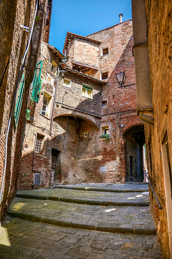 A suggestive and typical uphill alley in the historic heart of the medieval city of Siena in Tuscany, central Italy. Siena is one of the most beautiful Italian cities of art, in the heart of the Tuscan hills, famous for its immense artistic and historical heritage and for the Palio, where the seventeen old districts of the city compete every year in Piazza del Campo in one of the oldest horse racing in the world. Since 1995 the historic center of Siena has been declared a World Heritage Site by UNESCO. Image in high definition format.