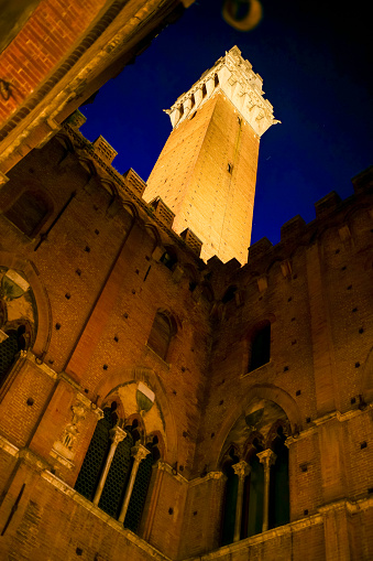 A suggestive night view of the Palazzo Pubblico (Town Hall) and the majestic Torre del Mangia (Mangia's Tower) in the famous Piazza del Campo, in the heart of the medieval city of Siena, in central Italy. Built starting in 1290, the Palazzo Pubblico was the seat of the Council of Nine and the executive power of the medieval city. Currently it is still the seat of the municipal government of the Tuscan city. Siena is one of the most beautiful Italian cities of art, in the heart of the Tuscan hills, in central Italy, famous for its immense artistic and historical heritage and for the Palio, where the seventeen districts of the city compete every year in Piazza del Campo in one of the oldest horse racing in the world. Since 1995 the historic center of Siena has been declared a World Heritage Site by UNESCO. Image in high definition format.