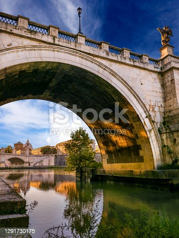 Rome, Italy -- The Tiber riverbank under the Sant'Angelo bridge, near the iconic Vatican City. On the horizon the St. Peter's Basilica dome silhouette. Image in High Definition format.
