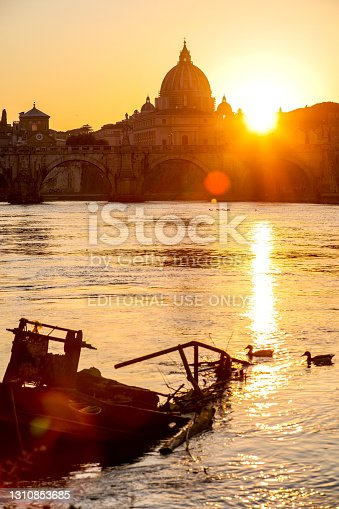 Rome, Italy, March 30 -- A suggestive winter sunset is reflected on the placid waters of the Tiber, creating an evocative play of lights with Ponte Sant'Angelo, the river bank and the majestic silhouette of the dome of St. Peter's Basilica. Image in high definition format.