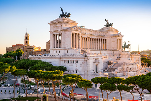 A suggestive sunset view of the Campidoglio or Capitoline Hill (Left), the ancient seat of the Roman Capitol, and the National Monument of the Altare della Patria (center), in the historic heart of Rome. Below, surrounded by the pine trees, the Imperial Forums Boulevard. The Capitoline Hill, one of the seven hills of Rome, was considered the sacred place for the Romans, between the Forum and the Campus Martius, where the majestic Temple of Capitoline Jupiter was erected. Currently the Palazzo del Campidoglio, with its characteristic bell tower, is the seat of the Municipality of Rome (Town Hall). The national monument of the Altare della Patria, or Vittoriano, was built in 1885 in neoclassical style in honor of the first King of Italy, Vittorio Emanuele II, between the north side of the Capitoline Hill and the central Piazza Venezia. Inside is the Tomb of the Unknown Soldier, a War Memorial dedicated to all the Italian soldiers who died in the war. The Altare della Patria is the scene of all the official Italian civic celebrations, in particular the Republic Day on June 2 and the Liberation Day on April 25. In 1980 the historic center of Rome was declared a World Heritage Site by Unesco. Image in high definition format.