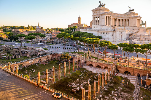 A suggestive sunset view of the Trajan's Forum (below) the Campidoglio or Capitoline Hill (up at center) and the National Monument of the Altare della Patria (right), in the historic heart of Rome. In the middle, surrounded by the pine trees, the Imperial Forums Boulevard. The area of the Roman Imperial Forums is one of the most iconic in Rome, visited by thousands of tourists every year, with the largest area of archaeological excavations in the world. The national monument of the Altare della Patria, or Vittoriano, was built in 1885 in neoclassical style in honor of the first King of Italy, Vittorio Emanuele II, between the north side of the Capitoline Hill and the central Piazza Venezia. Inside is the Tomb of the Unknown Soldier, a War Memorial dedicated to all the Italian soldiers who died in the war. The Altare della Patria is the scene of all the official Italian civic celebrations, in particular the Republic Day on June 2 and the Liberation Day on April 25. In 1980 the historic center of Rome was declared a World Heritage Site by Unesco. Image in high definition format.