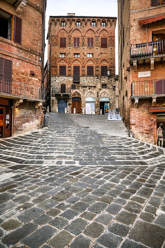 A suggestive view of a lovely corner in Piazza del Campo square, the medieval heart of Siena with its characteristic shell shape. Siena is one of the most beautiful Italian cities of art, in the heart of the Tuscan hills, in central Italy, famous for its immense artistic and historical heritage and for the Palio, where the seventeen districts of the city compete every year in Piazza del Campo in one of the oldest horse racing in the world. Since 1995 the historic center of Siena has been declared a World Heritage Site by UNESCO. Image in high definition format.