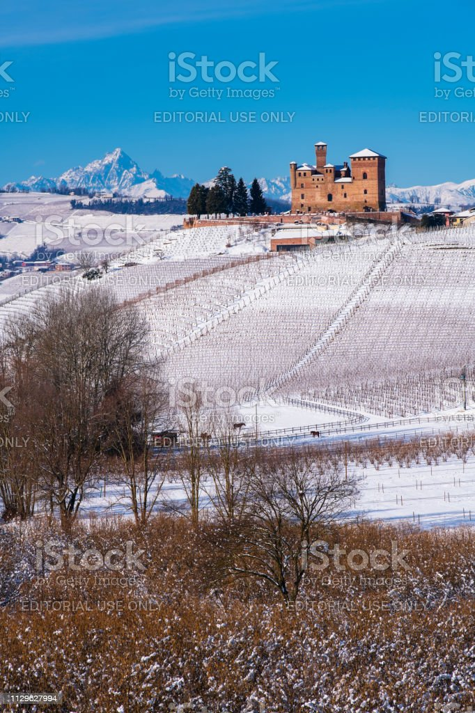 Suggestive view of the Unesco Castle of Grinzane Cavour on the snowy hills and vineyards - foto stock