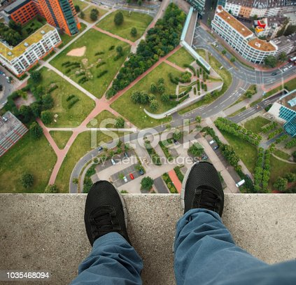 A man at the edge of a skyscraper