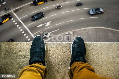 Two feet at the edge of a rooftop of a high building. A busy street appears looking down.