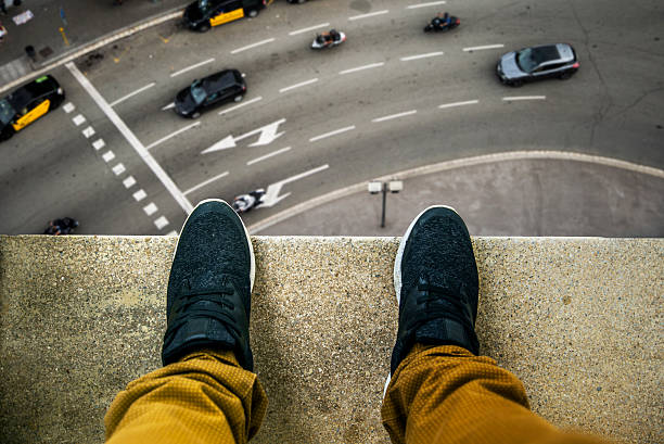Suicide about to jump Two feet at the edge of a rooftop of a high building. A busy street appears looking down. suicide stock pictures, royalty-free photos & images