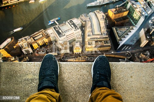 Two feet at the edge of a rooftop of a high building. Buildings and a river in the background.