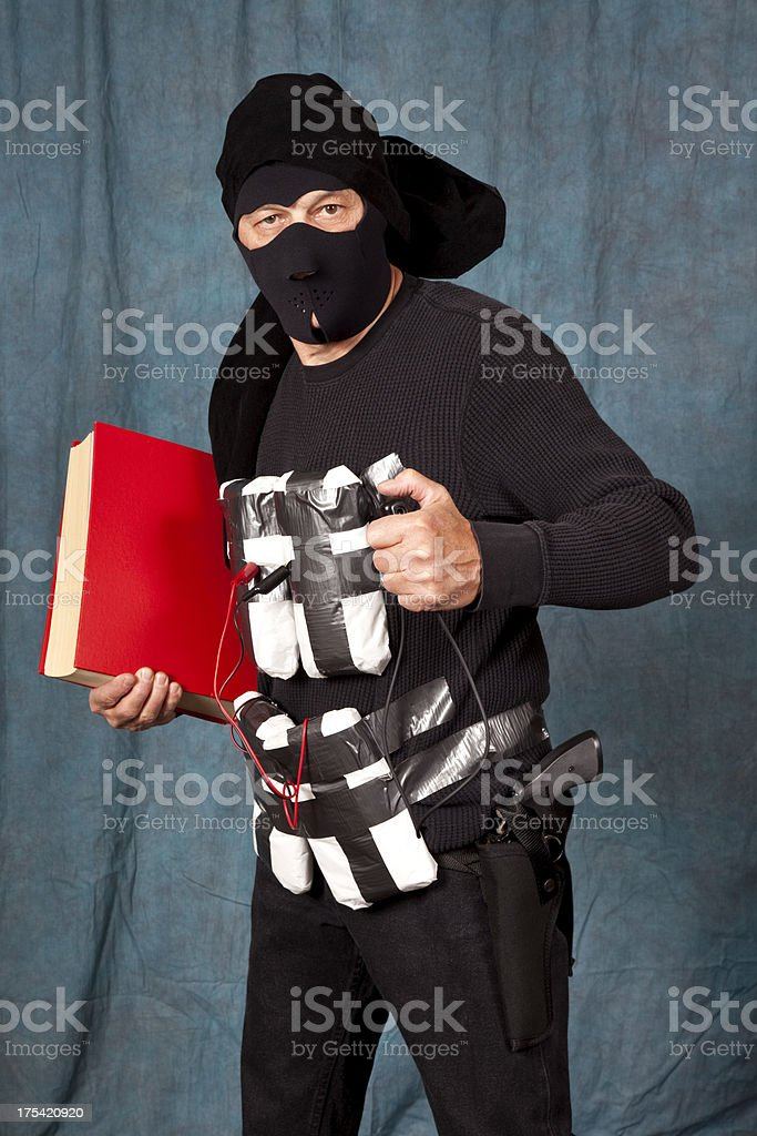 Suicide Bomber in black, explosives strapped to body holding book stock photo