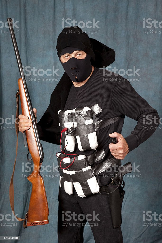 Suicide Bomber in black, explosives strapped to body holding shotgun stock photo