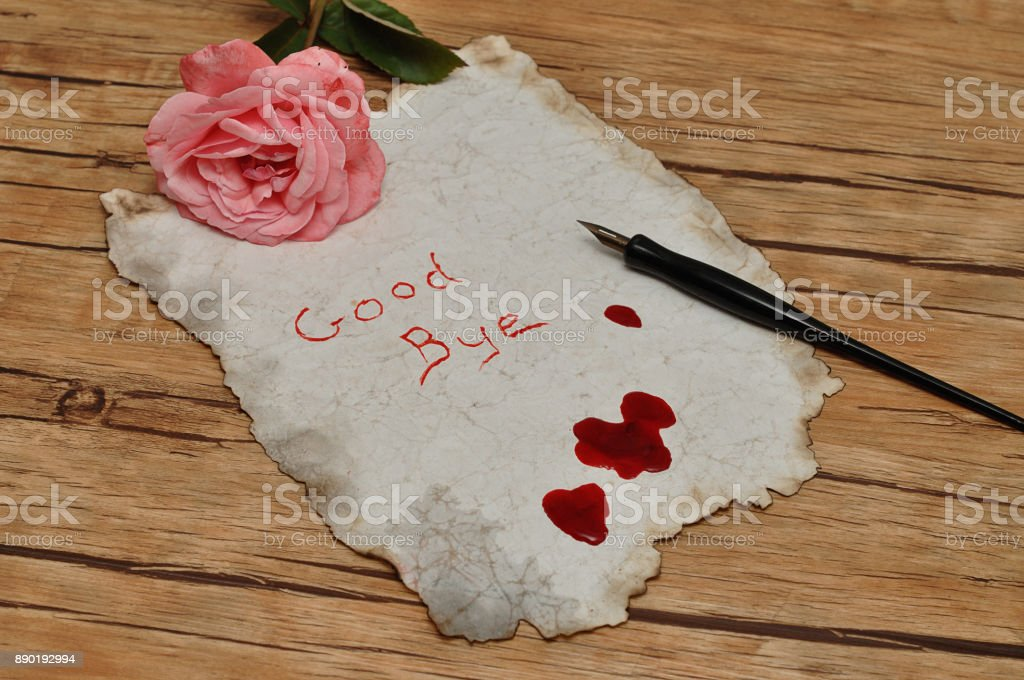 A suicide note on an old paper covered in blood with a vintage fountain pen and a pink rose stock photo