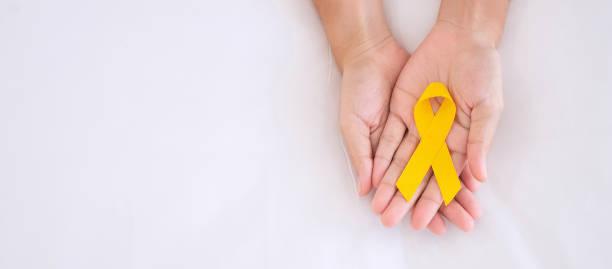 prevenção ao suicídio e conscientização do câncer infantil, fita amarela para apoiar pessoas vivendo e doentes. crianças conceito de dia do câncer e saúde mundial - setembro amarelo - fotografias e filmes do acervo