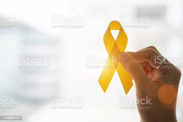 Photo of Suicide prevention and Childhood Cancer Awareness, Yellow Ribbon on wooden background  for supporting people living and illness. children Healthcare and World cancer day concept