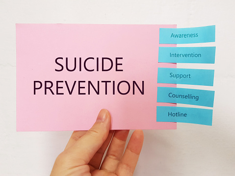A hand holding a red card with the word SUICIDE PREVENTION written on it