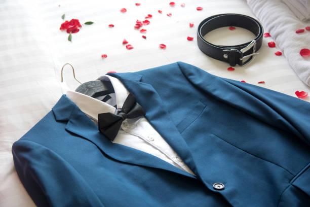 anzug und gürtel auf dem bett für eine trauung. - hochzeitsanzug herren stock-fotos und bilder