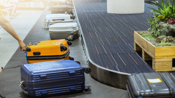 suit case on luggage conveyor belt at baggage claim in airport terminal. stock photo
