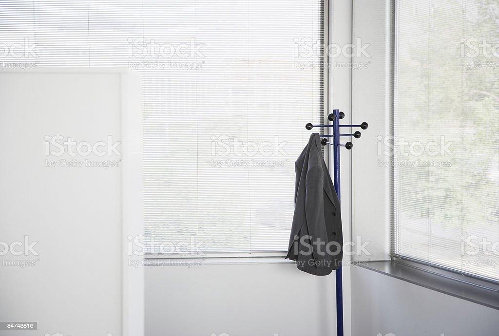 Suit jacket hanging on office coat rack stock photo
