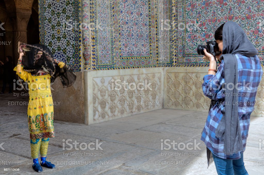 Suit photo session near entrance to the mosque, Shiraz, Iran. stock photo