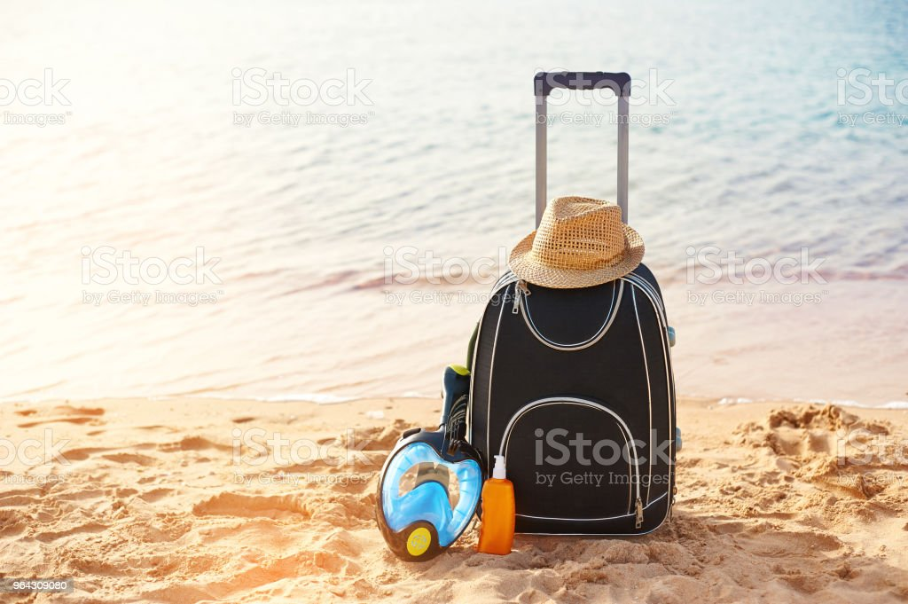 Suitcase and hat, sunscreen with a mask. The tropical sea, beach in...