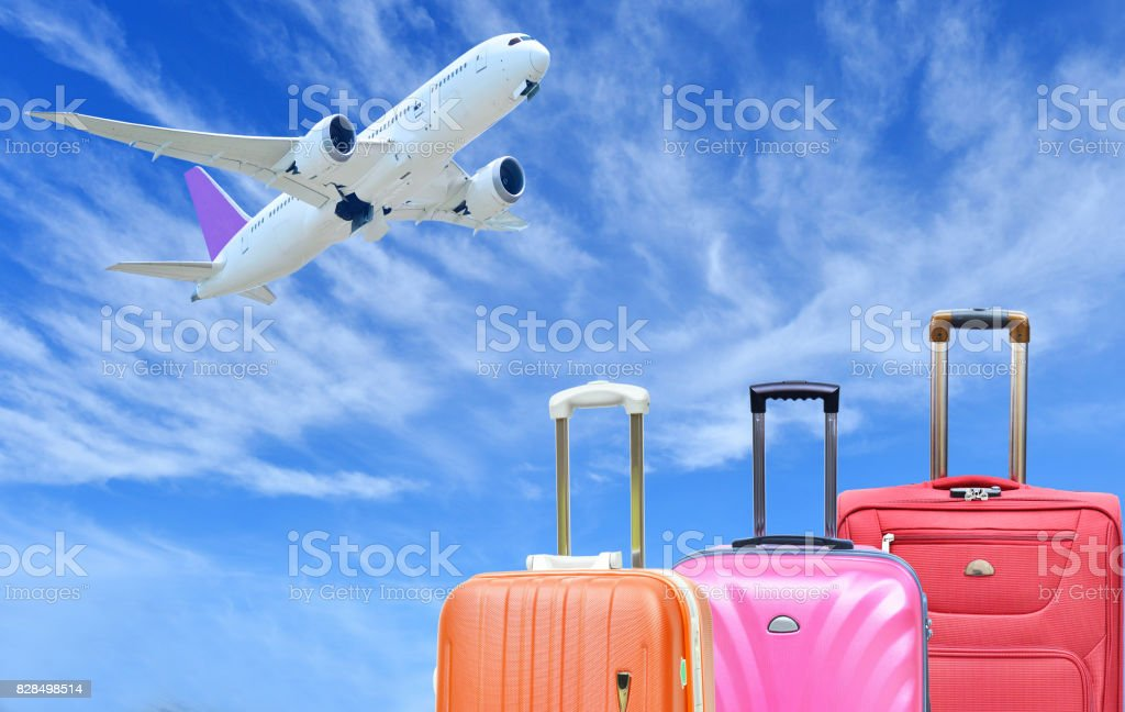 Suitcase and plane on sunny blue sky stock photo