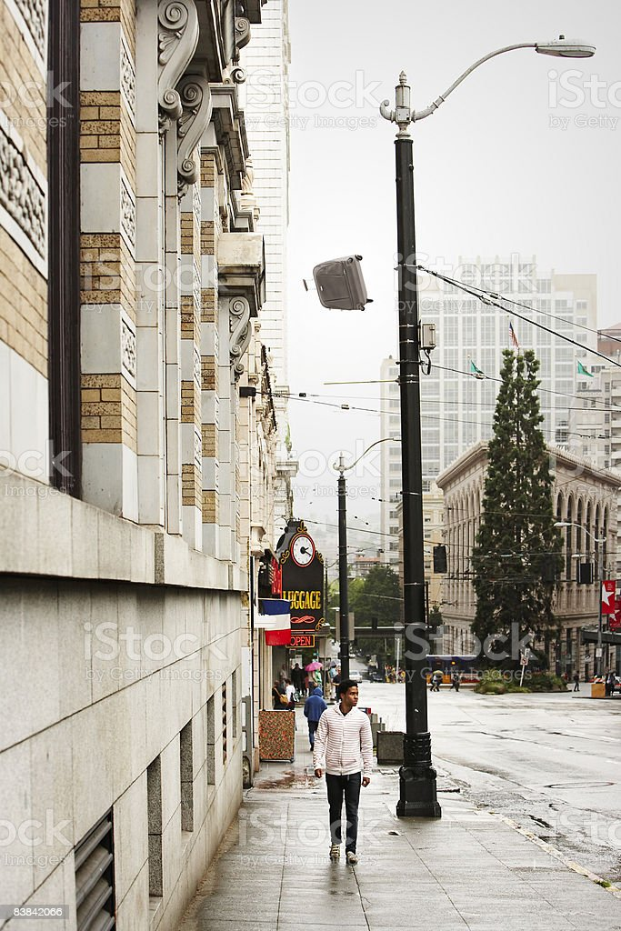 suitcase falling from building,man below unaware royalty-free stock photo