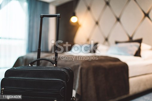 A black closed suitcase in a modern hotel room with lights on, brown, white and blue bedding and big windows.