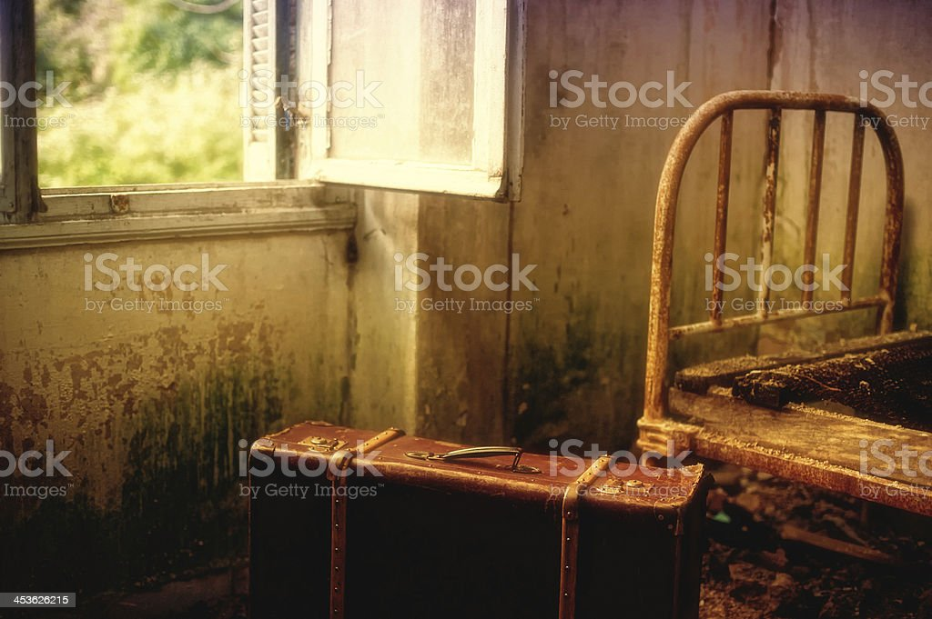 Suitcase in an empty dirty room stock photo