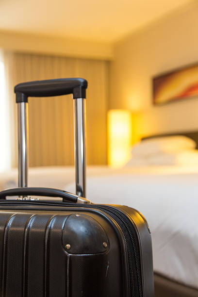 suitcase in hotel room stock photo