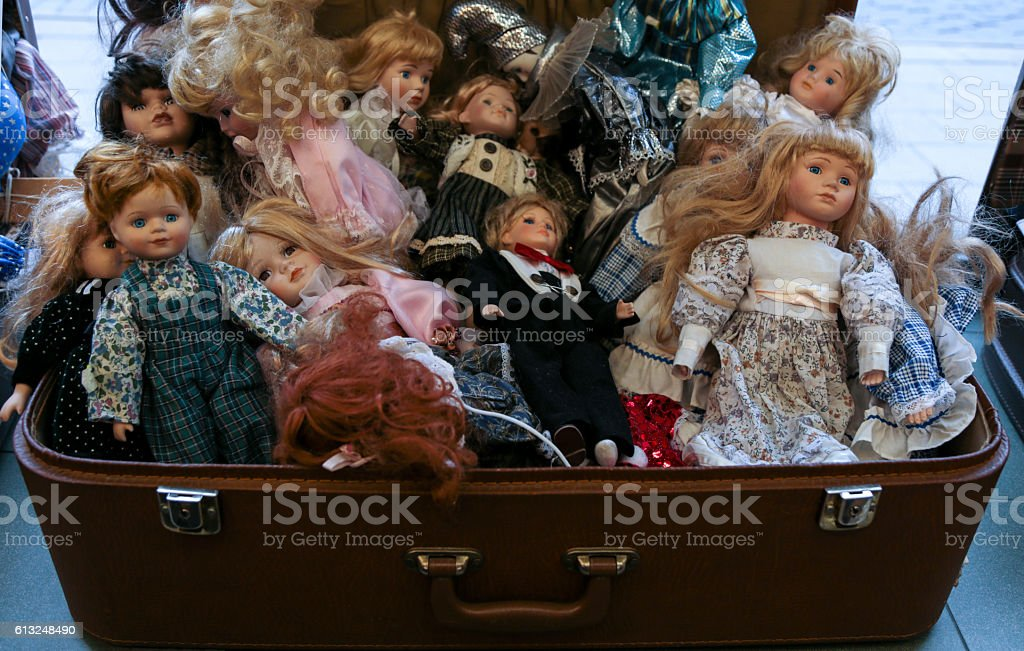 suitcase  , old porcelain dolls stock photo