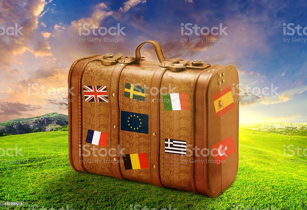 Suitcase on flags with landspace stock photo