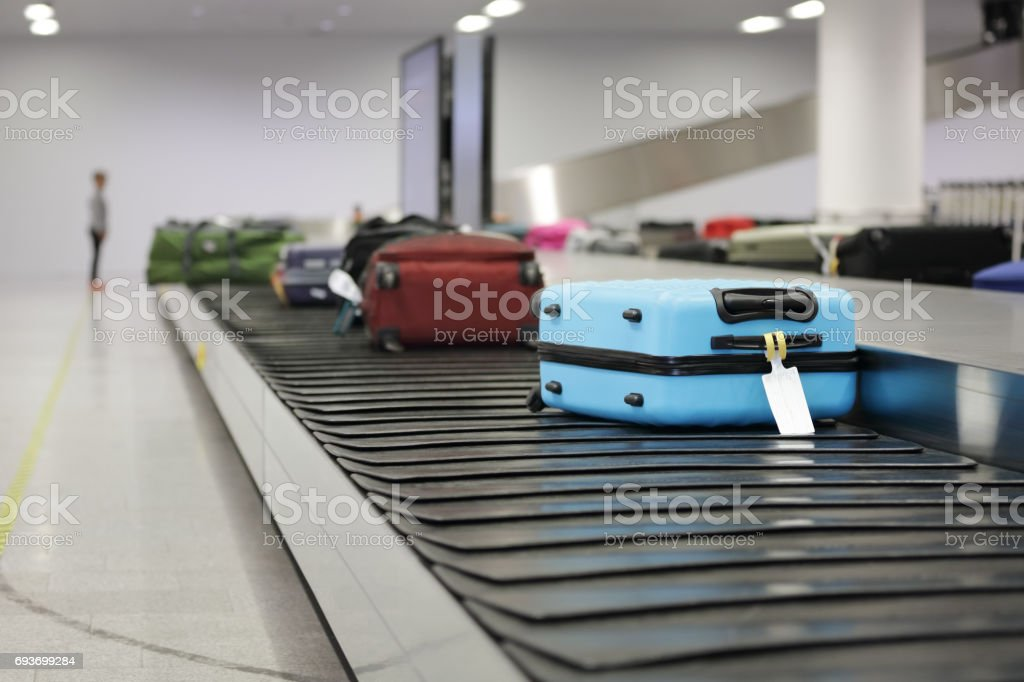 Suitcase or luggage on conveyor belt in the airport stock photo
