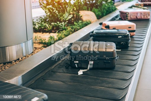 istock Suitcase or luggage with conveyor belt in the international airport. 1009914672