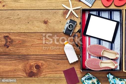 941183588 istock photo Suitcase packed for beach vacation on wood with digital tablet 624529410