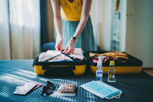 Woman packing suitcase for summer trip, including face masks and travel-sized antibacterial hand gels