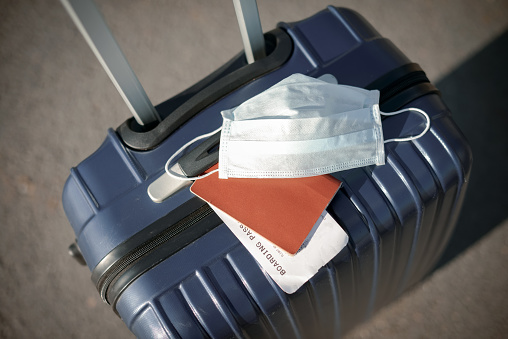 suitcase, passport and medical mask
