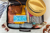 Suitcase prepared to travel in summer, in the new normal, after the coronavirus covid 19 pandemic, with a face mask among the luggage. There are other accessories like a hat, sunglasses, camera. Concept of quarantine, coronavirus, summer vacation in new normal. Flat lay or top view