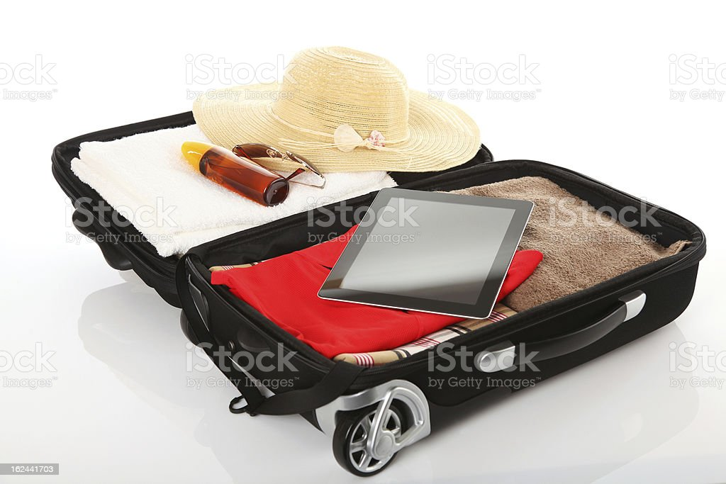 Suitcase with hat, clothes and iPad packed stock photo