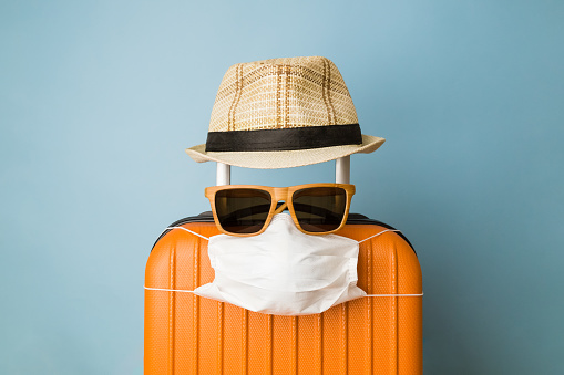 Suitcase with hat, sunglasses and protective medical mask on pastel blue background minimal creative coronavirus covid-19 travel concept.